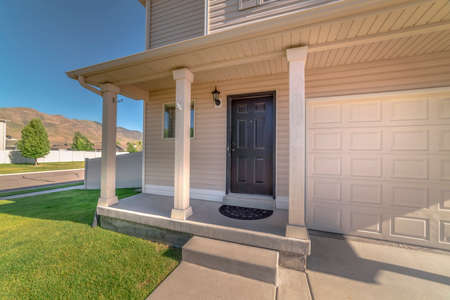 Home facade with concrete porch and front door adjacent to the garage door. The home has white wall sidein, spacious lawn, and view of road, mountain, and blue sky. Stock Photo