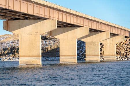 Enorme landhoofden die de overspanning van een balkbrug over blauw meerwater ondersteunen. Op de achtergrond is rotsachtig en besneeuwd land tegen de lucht te zien. Stockfoto