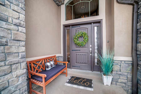 Beautiful home entrance with gray door sidelights and huge transom window. Stone brick wall, wooden bench, doormat, potted plant, and wreath can also be seen at this facade.