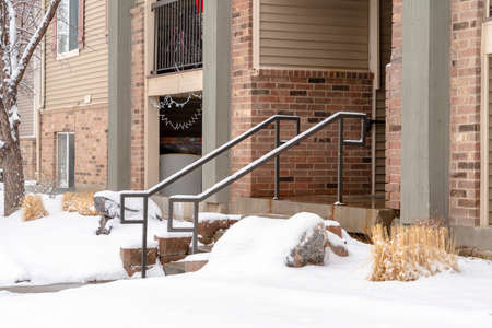 Yard and stone stairs covered with snow at the residential building entrance. Snowy trees and grasses can also be seen in front of the brick home with balcony. Stock fotó