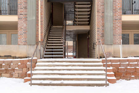 Residential building entrance with snow covered stairs and yard during winter. Flight of indoor stairs, balconies, and brick wall can also be seen at the facade of this residence. Stock fotó