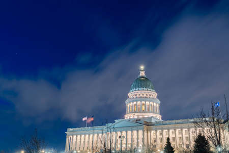 Facade of majestic Utah State Capital Building glowing against sky and clouds. The famous landmark with stunning architecture in Salt Lake City, Utah.