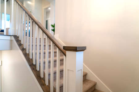 Indoor staircase of a home with white balusters brown handrail and newel. The treads are covered with gray carpet and leads to the upper floor. Banque d'images