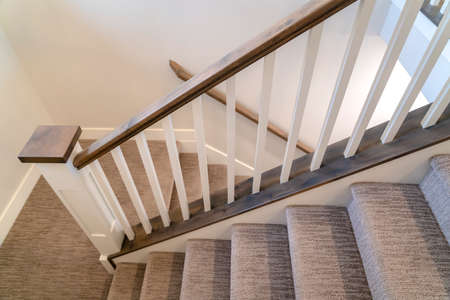 U shaped indoor staircase of home with treads and landing covered with carpet. The stairs has white balusters, wooden handrail, and brown newel.