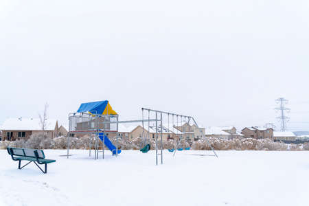 Neighborhood park with vibrant playground that contrasts against snow in winter. Cloudy sky and houses with snowy roofs can be seen in the background.