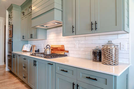 Kitchen interior with cooktop on white counter top under hanging cabinets. Kitchen appliances, wooden floor, and tile backsplash can also be seen inside this room.