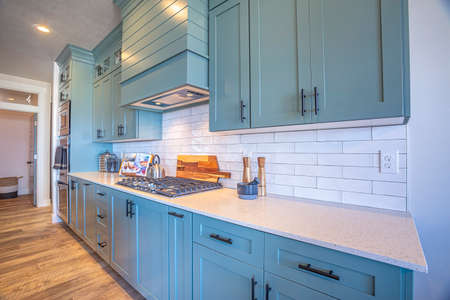 Kitchen with white counter top and bluish gray cabinets against tile backsplash. Modern cooking appliances and wooden floor can also be seen inside this room.