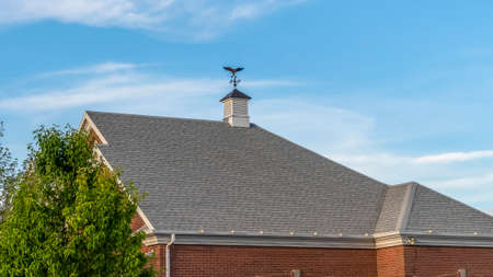 Panorama frame Exterior of building with cupola and compass on the gray pitched roof. The building has red brick wall and cloudy blue sky can be seen in the bakcground.