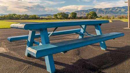 Panorama frame Blue wood picnic table with seats under the white roof of a park pavilion. Beautiful scenery of grassy land, roads, trees, mountain, and cloudy blue sky cna be seen on this sunny day.