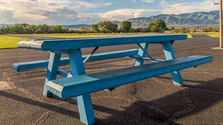 Panoramarahmen Blauer Holzpicknicktisch mit Sitzgelegenheiten unter dem weißen Dach eines Parkpavillons. An diesem sonnigen Tag ist eine wunderschöne Landschaft mit Grasland, Straßen, Bäumen, Bergen und bewölktem blauem Himmel zu sehen.