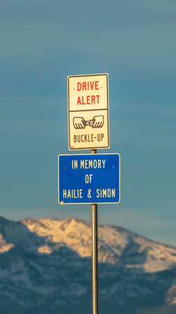 Vertical Drive Alert and Buckle Up road sign against snowy mountain and cloudy sky. A road guardrail and safety barrier can be seen bellow the signage.