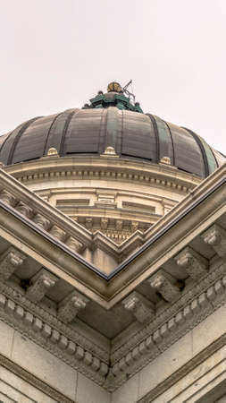Vertical frame Utah State Capitol building and dome in Salt Lake City against bright cloudy sky. Decorative mouldings can be seen at the exterior walls of the famous structure.