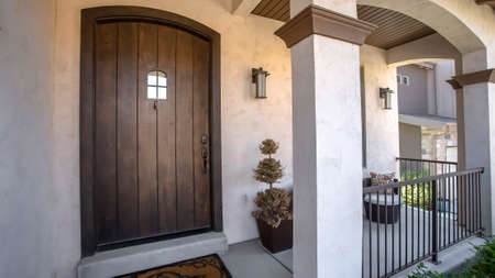 Panorama Brown wood arched front door with glass panes at the facade of home with porch. Square columns, railings, chair, plants, wall lamps, and dormat can also be seen at the exterior of this house.