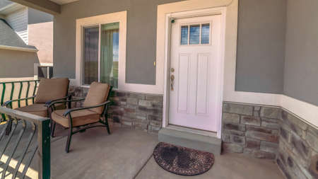 Panorama Entrance of home with chairs at the porch and front door with glass panes. Window and security camera can also be seen at the facade of this house.