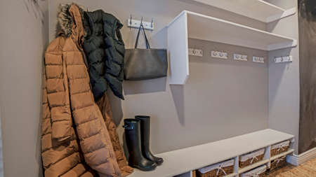 Panorama frame Walk in closet with clothes bag and shoes on the built in shelves and hangers. The storage room has white wall and brown carpet on the floor. Stock Photo