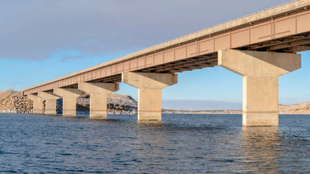 Panorama Stringer puente que atraviesa un lago con vistas al terreno nevado y cielo nublado. El tablero del puente de vigas está sostenido por pilares o estribos. Foto de archivo