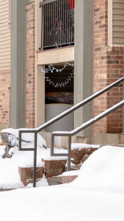 Photo Vertical Yard and stone stairs covered with snow at the residential building entrance. Snowy trees and grasses can also be seen in front of the brick home with balcony.