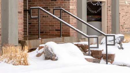 Photo Panorama frame Yard and stone stairs covered with snow at the residential building entrance. Snowy trees and grasses can also be seen in front of the brick home with balcony.