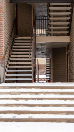Photo Vertical Residential building entrance with snow covered stairs and yard during winter. Flight of indoor stairs, balconies, and brick wall can also be seen at the facade of this residence.