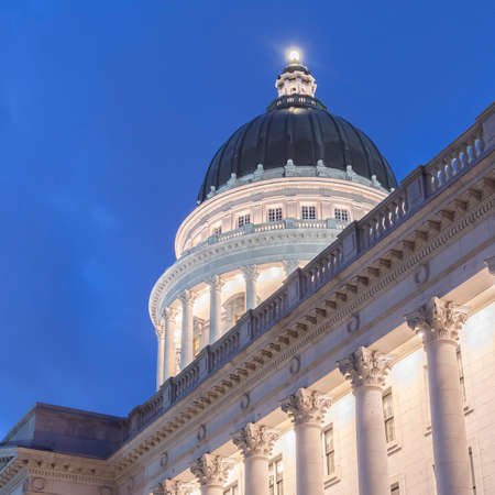 Photo Square frame Facade of famous Utah State Capital Building glowing against vivid blue sky. The majestic structure boasts a beautiful architecture with dome, columns, and white stone wall.
