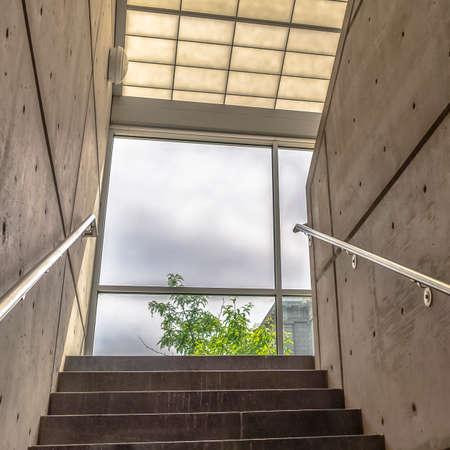 Cornice quadrata Scale tra le pareti interne dell'edificio che portano alla parete di vetro con vista sul cielo. In questa immagine si possono vedere anche un corrimano in metallo, un'applique rotonda e un tetto in vetro.