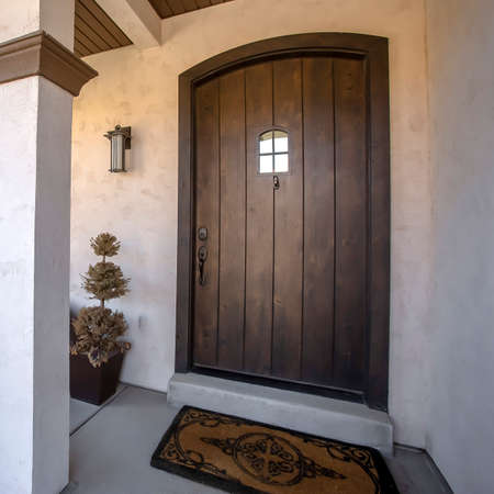 Square Brown wood arched front door with glass panes at the facade of home with porch. Square columns, railings, chair, plants, wall lamps, and dormat can also be seen at the exterior of this house. Stock fotó