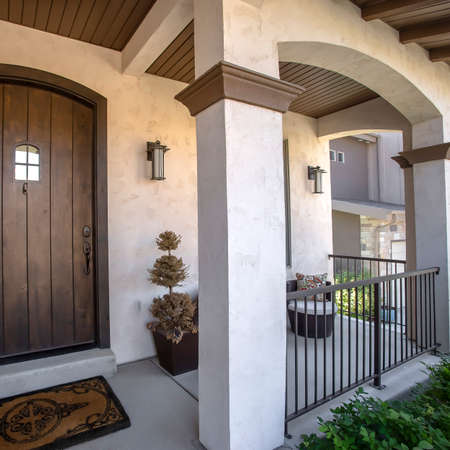 Square frame Brown wood arched front door with glass panes at the facade of home with porch. Square columns, railings, chair, plants, wall lamps, and dormat can also be seen at the exterior of this house. Stock fotó