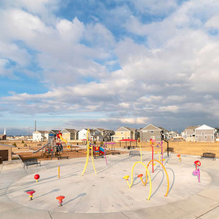 Square frame Colorful childrens playground against houses and overcast blue sky in winter Foto de archivo