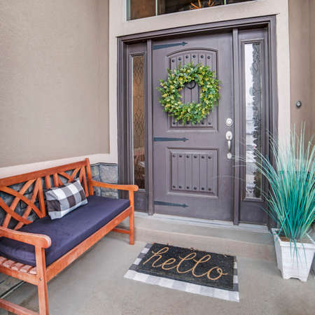 Square Beautiful home entrance with gray door sidelights and huge transom window. Stone brick wall, wooden bench, doormat, potted plant, and wreath can also be seen at this facade.
