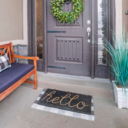 Square frame Beautiful home entrance with gray door sidelights and huge transom window. Stone brick wall, wooden bench, doormat, potted plant, and wreath can also be seen at this facade.