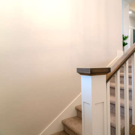 Square frame Indoor staircase of a home with white balusters brown handrail and newel. The treads are covered with gray carpet and leads to the upper floor.