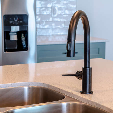 Photo Square frame Black faucet and stainless steel double basin sink on the home kitchen island. Refrigerator with ice and water dispenser, counter, and white wall can be seen in the background.