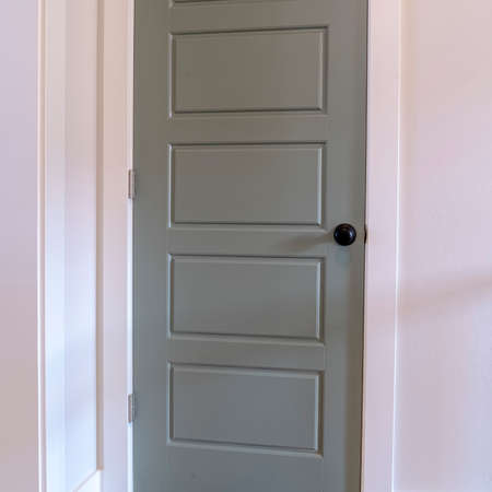 Square Gray door with matte black door knob and white door frame against wall. Architectural details inside a house with brown wooden floor.