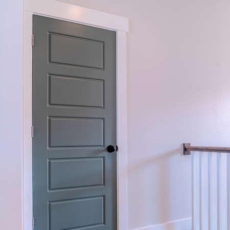 Square Home interior with brown wooden floor railing and gray door against white wall. The glossy wooden door has a matt black door knob. Standard-Bild