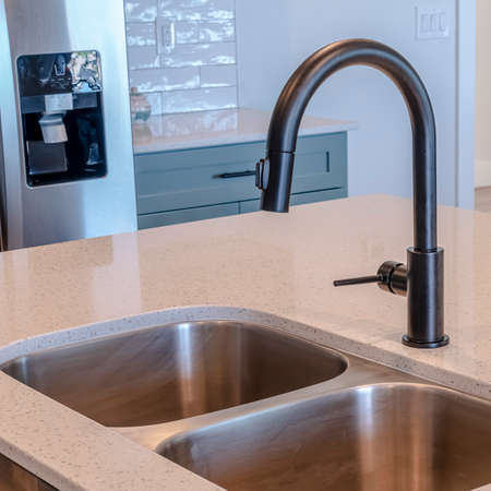 Square frame Black faucet and stainless steel double basin sink on kitchen island of home. Front door, wood floor, and refrigerator can be seen in the bakcground.