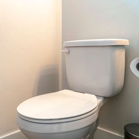 Photo Square Toilet beside a trash can and bathroom cabinet with tissue roll holder. White countertop and hanging towet can also be seen inside this bathroom.