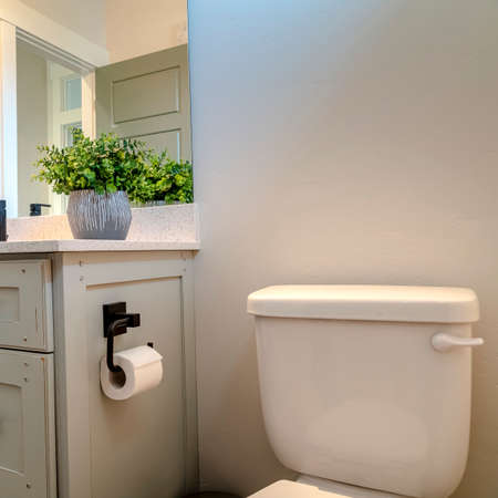 Photo Square frame Vanity cabinet and toilet inside the bathroom of home with white wall