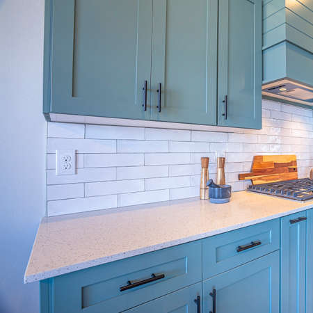 Square frame Kitchen with white counter top and bluish gray cabinets against tile backsplash. Modern cooking appliances and wooden floor can also be seen inside this room.