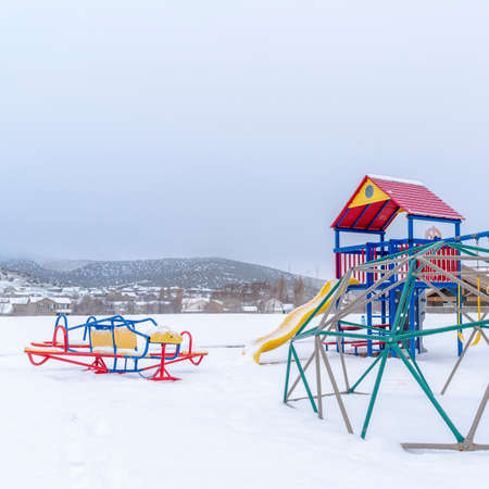 Photo Square Colorful playground that contrasts against the snow covered winter landscape. Houses, hills, and cloudy sky can be seen in the background.