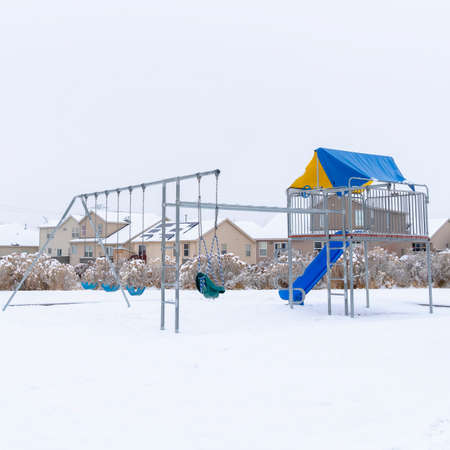 Photo Square Neighborhood park with vibrant playground that contrasts against snow in winter. Cloudy sky and houses with snowy roofs can be seen in the background. Banque d'images