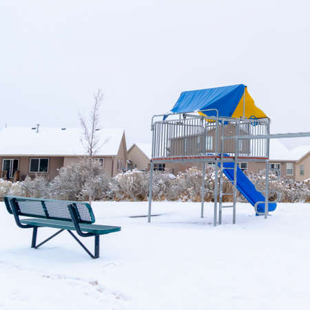 Square frame Neighborhood park with vibrant playground that contrasts against snow in winter. Cloudy sky and houses with snowy roofs can be seen in the background. Banque d'images