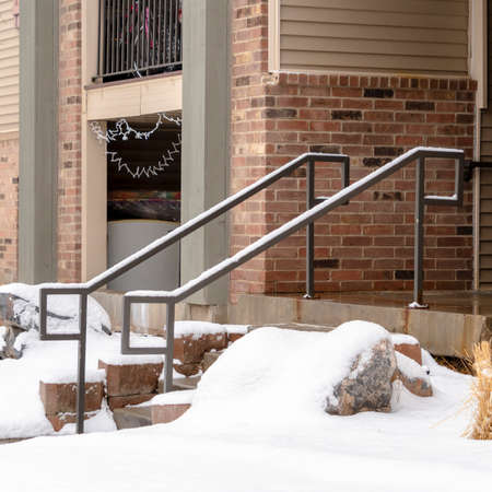 Square frame Yard and stone stairs covered with snow at the residential building entrance. Snowy trees and grasses can also be seen in front of the brick home with balcony. Stock fotó