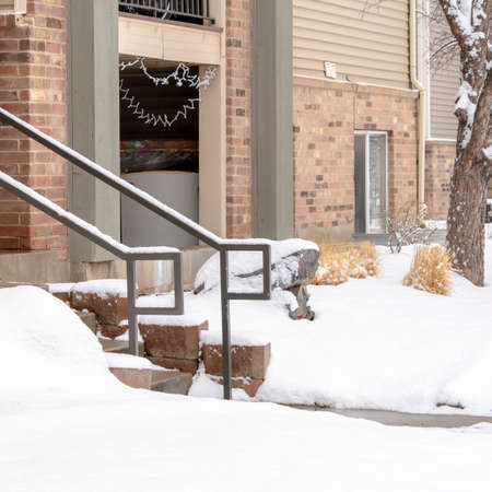Photo Square Yard and stone stairs covered with snow at the residential building entrance. Snowy trees and grasses can also be seen in front of the brick home with balcony.