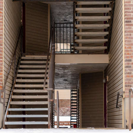 Square Residential building entrance with snow covered stairs and yard during winter. Flight of indoor stairs, balconies, and brick wall can also be seen at the facade of this residence. Stock fotó