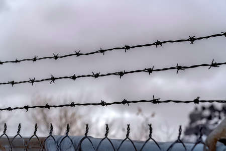 Sharp barbed wires of rusty chain link fence with blurred cloudy sky background. Focus on a security fence of a private property against blurry skyscape.
