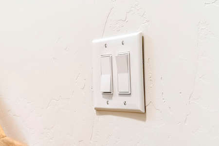 Wall mounted electrical rocker light switch with multiple flat broad levers. The cover plate of the lighting controls is screwed on the white wall.