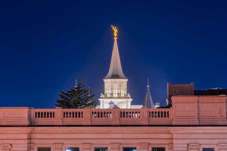 Provo City Center Temple with statue of angel and spire against blue evening sky. Exterior view of the temple of The Church of Jesus Christ of Latter-day Saints in Utah at night.