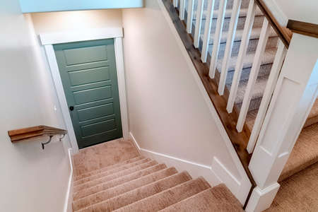 Carpeted U shaped staircase that leads down to the basement door of a home. The stairs have brown handrail that is supported by white balusters.