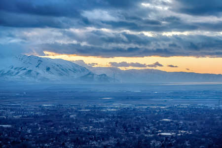Salt Lake City Utah landscape against snowy mountain and cloudy sky at sunset. The city has a view of scenic nature and glowing golden sky.