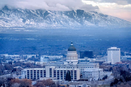 Utah State Capital Building against steep snowy mountain and gray cloudy sky. Gloomy downtown Salt Lake City landscape surrounded by scenic nature views.